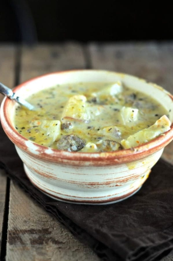 A bowl of potatoes and ground beef in a cheesy broth with a rustic wood background