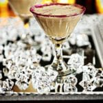 A martini glass with red glitter on the rim filled with a chocolate martini. Glass cubes on a platter.