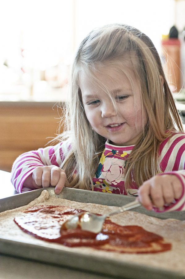 Little Girl Spreading Pizza Sauce on Pizza Dough