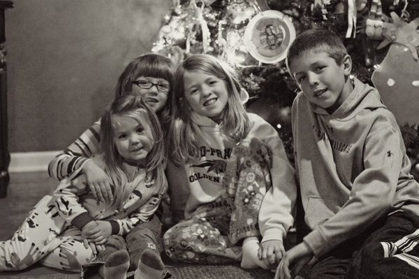 Kids sitting in front of the Christmas tree