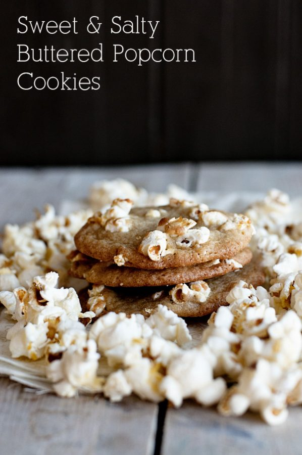 3 stacked cookies embedded with popcorn on a table surrounded by popcorn and a black background