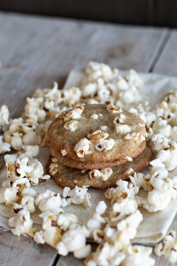 3 stacked cookies embedded with popcorn on a napkin and table surrounded by popcorn
