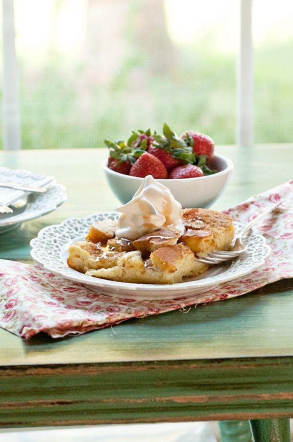 French Toast Casserole on a white plate by a window. A bowl of strawberries and cloth napkin.