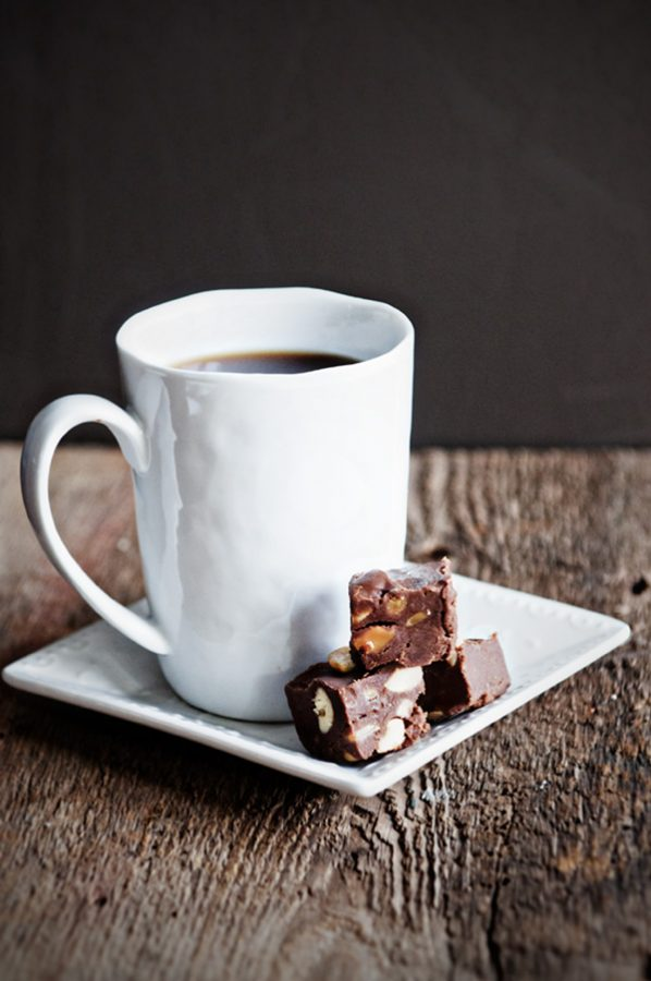 Coffee cup on a white plate with three pieces of chocolate cashew fudge