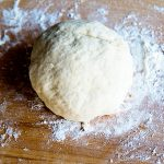 A ball of pizza dough on a wooden cutting board
