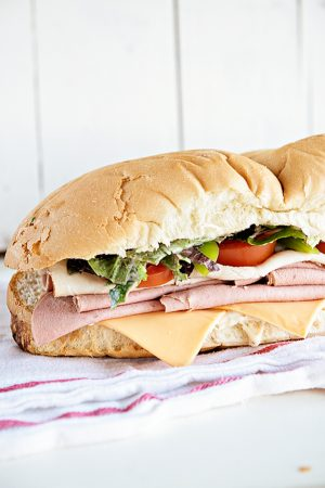 Hero Sub Sandwich recipe with super simple sauce. This is a great game day idea for a crowd! From dineanddish.net