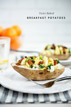 Twice Baked Breakfast Potatoes with eggs, bacon and spinach served on a white plate with white brick background