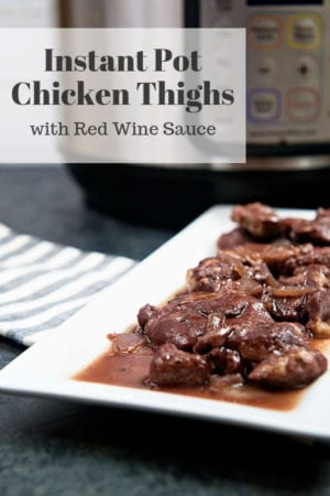 An instant pot with chicken thighs in red wine sauce on a white platter.
