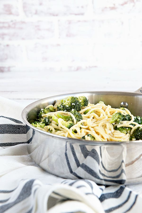 Spaghetti and broccoli in a silver pan with a white brick background