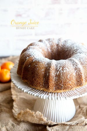 Bundt Cake on a white cake stand with white background and oranges