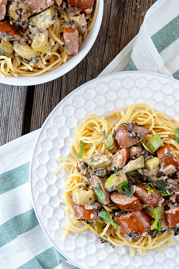White plate loaded with spaghetti and a creamy mushroom sauce