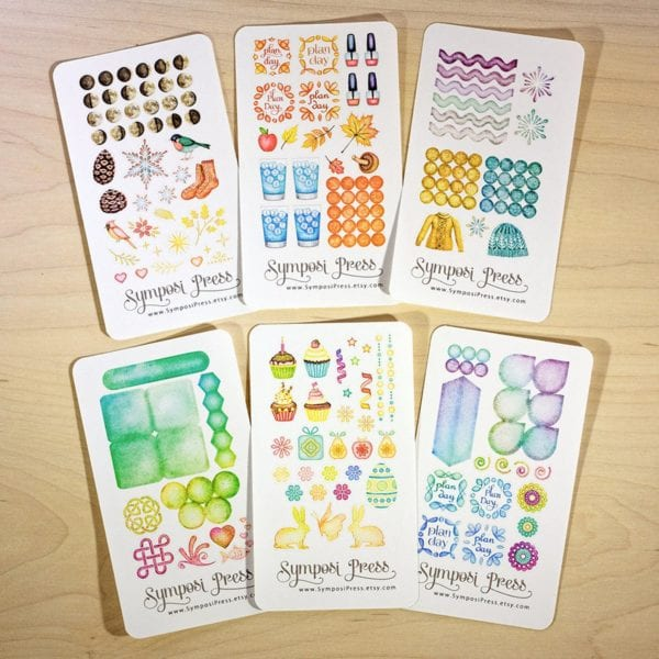 6 sticker sheets on wood background from Symposi Press Etsy store