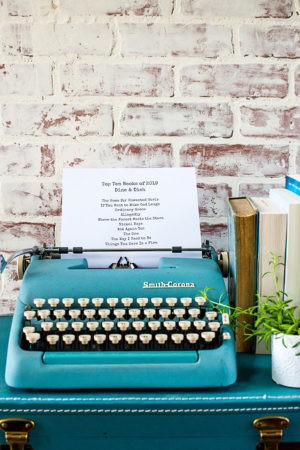 Typewriter sitting on a suitcase with books and a plant nearby and a list of favorite books read in 2019