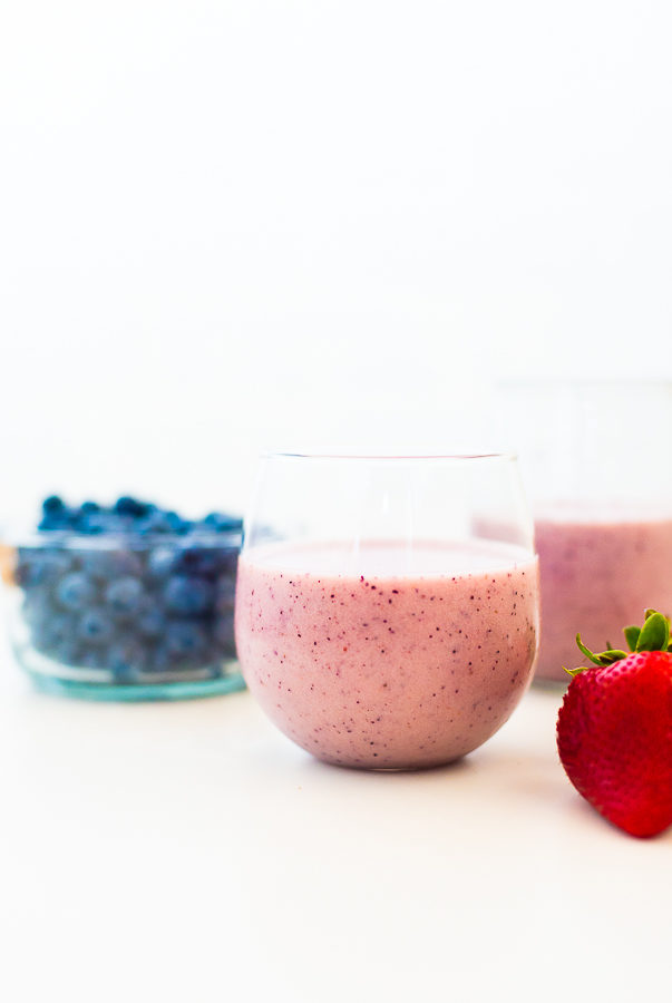 white background with two glasses filled with berry smoothies and a bowl of blueberries