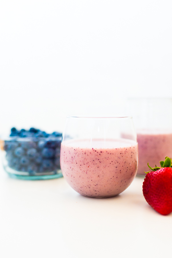 white background with two glasses filled with a strawberry blueberry smoothie and a bowl of blueberries