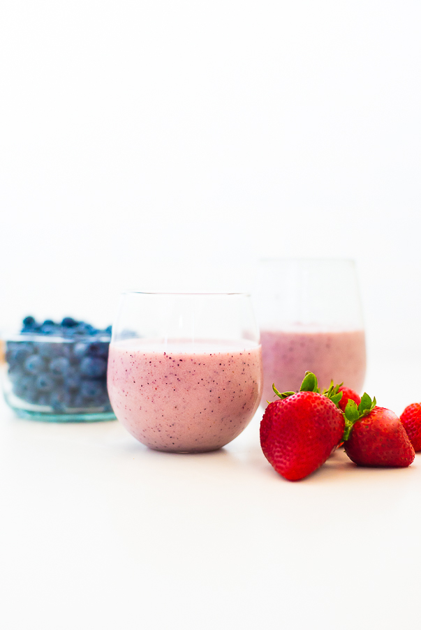 White background with two glasses of pink smoothies with strawberries and blueberries