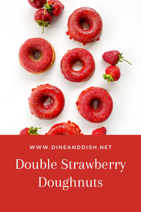 white background with several bright pink strawberry doughnuts and fresh strawberries